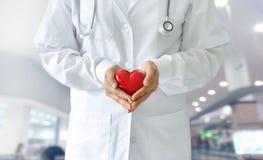 Docteur de médecine tenant la forme rouge de coeur, techno médicale photos libres de droits