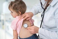 Docteur de pédiatre examinant une petite fille par le stéthoscope photos stock