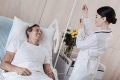 Docteur de sourire ajustant le compteur de baisse au patient masculin malade Images stock