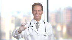Docteur de sourire avec la seringue, fond brouillé banque de vidéos