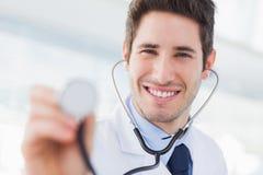 Docteur de sourire avec son stéthoscope regardant l'appareil-photo Image libre de droits
