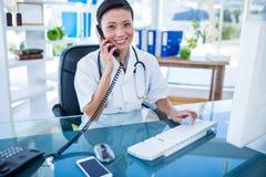 Docteur de sourire ayant l'appel téléphonique et à l'aide de son ordinateur Image stock