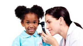 Docteur de sourire contrôlant les oreilles de son patient Photographie stock