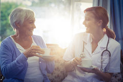Docteur de sourire et parler patient tout en ayant le thé photographie stock