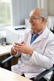 Docteur de sourire heureux au bureau médical dans l'hôpital Photographie stock