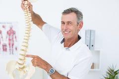 Docteur de sourire montrant l'épine anatomique Photo libre de droits