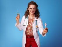 Docteur de sourire de pediatrist avec la seringue et le lollypop sur le bleu photographie stock