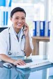 Docteur de sourire regardant l'appareil-photo et avoir l'appel téléphonique Photos libres de droits