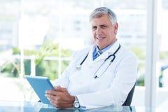 Docteur de sourire s'asseyant à son bureau et à tenir le comprimé Image libre de droits