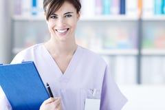 Docteur de sourire tenant des rapports médicaux Photographie stock libre de droits