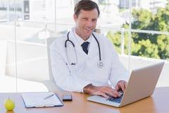 Docteur de sourire travaillant sur un ordinateur portable Photos libres de droits