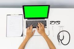 Docteur de vue supérieure travaillant dur au bureau avec l'eq vert d'ordinateur portable d'écran Photographie stock
