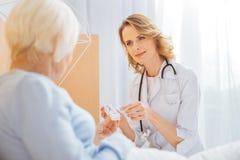 Docteur digne de confiance attentif parlant à son patient âgé et semblant amical Photos stock