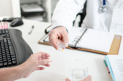 Docteur donnant des pillules à son patient images libres de droits