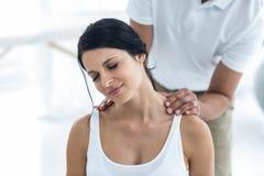 Docteur donnant la physiothérapie à la femme enceinte photographie stock