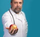 Docteur donnant la pomme pour la consommation saine Photographie stock libre de droits