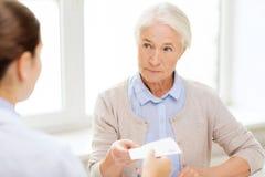 Docteur donnant la prescription à la femme supérieure Photographie stock libre de droits