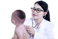 Docteur donnant le contrôle avec le stéthoscope au bébé Image stock