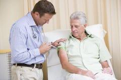 Docteur donnant le pointeau d'homme dans la chambre d'examen Image stock