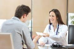Docteur donnant une prescription à son patient Photographie stock