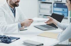 Docteur donnant une prescription ? un patient photographie stock libre de droits