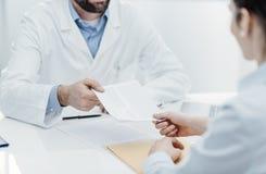 Docteur donnant une prescription ? un patient image libre de droits
