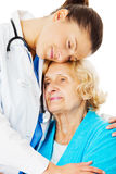 Docteur Embracing Senior Woman au-dessus du fond blanc Image stock