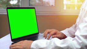 Docteur employant le touchpad d'ordinateur portable, carnet avec une clé verte de chroma d'écran banque de vidéos