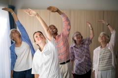 Docteur et aînés féminins de sourire s'exerçant avec des bras augmentés Photographie stock