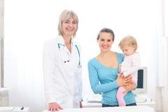 Docteur et mère pédiatriques aînés avec la chéri Photographie stock libre de droits