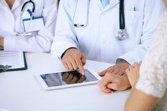 Docteur et parler patient tout en se reposant au bureau dans le bureau Médecin se dirigeant dans l'ordinateur ou la table de pavé Photos stock