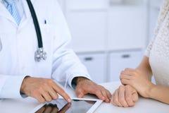 Docteur et parler patient tout en se reposant au bureau dans le bureau Médecin se dirigeant dans l'ordinateur ou la table de pavé Image stock