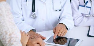 Docteur et parler patient tout en se reposant au bureau dans le bureau Médecin se dirigeant dans l'ordinateur ou la table de pavé Photos libres de droits