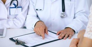 Docteur et parler patient tout en se reposant au bureau dans le bureau Médecin se dirigeant dans la forme d'antécédents médicaux  Photographie stock