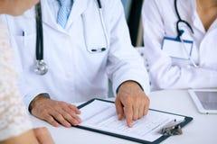Docteur et parler patient tout en se reposant au bureau dans le bureau Médecin se dirigeant dans la forme d'antécédents médicaux  Images stock