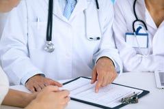 Docteur et parler patient tout en se reposant au bureau dans le bureau Médecin se dirigeant dans la forme d'antécédents médicaux  Image stock