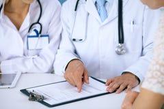 Docteur et parler patient tout en se reposant au bureau dans le bureau Médecin se dirigeant dans la forme d'antécédents médicaux  Image libre de droits