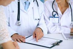Docteur et parler patient tout en se reposant au bureau dans le bureau Médecin se dirigeant dans la forme d'antécédents médicaux  Photo stock