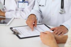 Docteur et parler patient tout en se reposant au bureau dans le bureau Médecin se dirigeant dans la forme d'antécédents médicaux  Images libres de droits