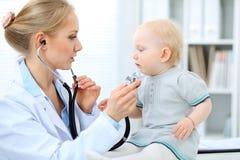 Docteur et patient dans l'hôpital La petite fille est examinée par le pédiatre avec le stéthoscope Médecine et soins de santé Image stock