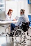 Docteur et patient dans le fauteuil roulant Photo libre de droits