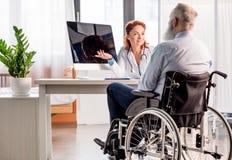Docteur et patient dans le fauteuil roulant Photos stock