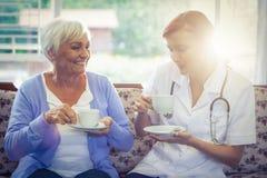 Docteur et patient de sourire ayant le thé photo stock