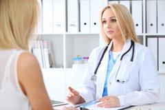 Docteur et patient discutant quelque chose tout en se reposant à la table Concept de médecine et de soins de santé Photographie stock libre de droits
