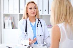 Docteur et patient discutant quelque chose tout en se reposant à la table à l'hôpital Concept de médecine et de soins de santé photos libres de droits