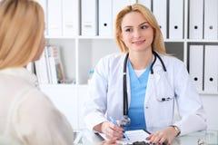 Docteur et patient discutant quelque chose tout en se reposant à la table à l'hôpital Concept de médecine et de soins de santé photographie stock libre de droits
