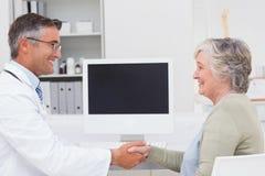 Docteur et patient féminin se serrant la main photo stock