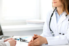 Docteur et patient s'asseyant au bureau Image libre de droits