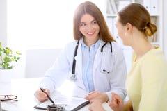 Docteur et patient s'asseyant au bureau près de la fenêtre Photo libre de droits