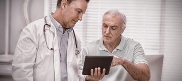 Docteur et patient supérieur à l'aide du comprimé numérique photographie stock